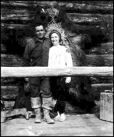 couple posing with grizzly hide