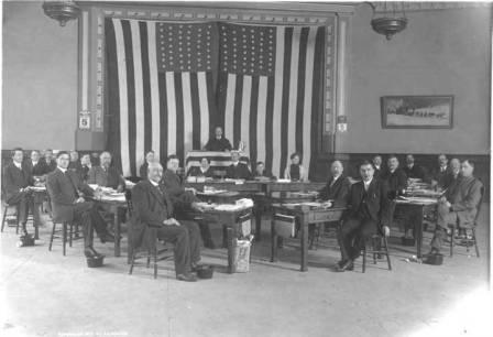 The First Territorial House of Representatives at the Elks Hall in Juneau.  Presiding officer E. B. Collins is standing in the center, circa March 1913/> <table border=