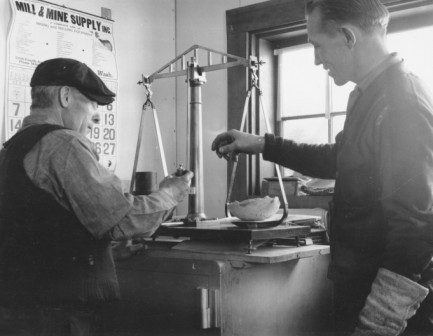 George Lynch (left) and a young engineer weighing a retort sponge at the Independence Mine, circa 1937.